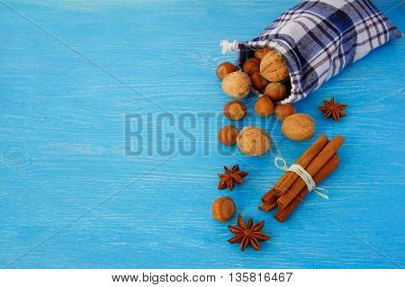Christmas nuts and spices in bag on blue background