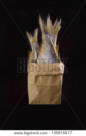 Dried fish in a paper bag on a dark background
