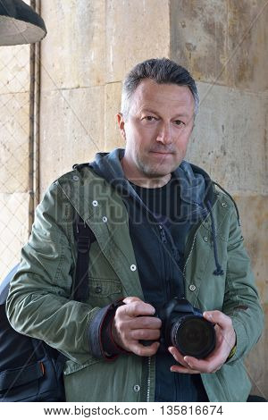 Professional photographer with photo camera outdoor against ancient obsolete wall, while working