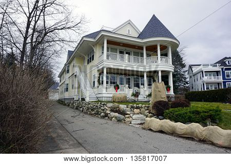 HARBOR SPRINGS, MICHIGAN / UNITED STATES - DECEMBER 24, 2015: A large yellow mansion near the Zorn Park Beach in Harbor Springs.