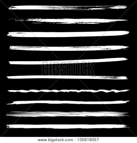 Large collection or set of artistic white paint hand made creative brush strokes isolated on black background