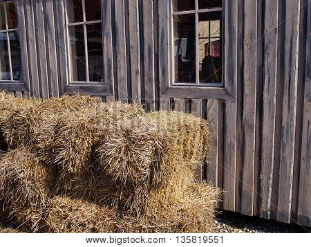 Old black wooden barn on a farm with straw hay stacks outside