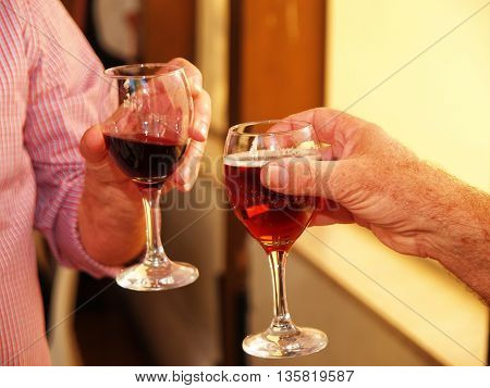 Friends toasting with two glasses of red wine in a social event party