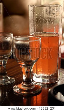 Half-full glass of ale on table close-up view and empty vodka glasses in dark room.