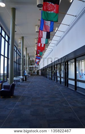 JOLIET, ILLINOIS / UNITED STATES - OCTOBER 25, 2015: National flags decorate the principal hallway at Joliet Junior College.