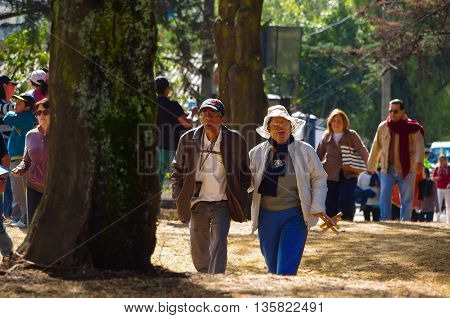 QUITO, ECUADOR - JULY 7, 2015: Two adults with sun protection walking through a park to arrive to pope Francisco mass.