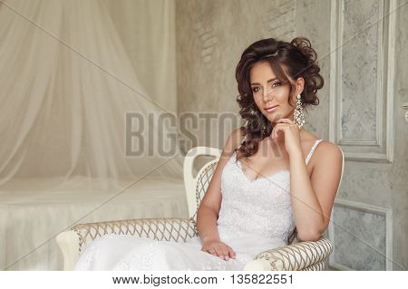 Beautiful Bride With Perfect Makeup And Hairstyle Sitting In Armchair.