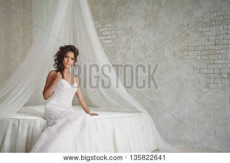 Beautiful Bride With Perfect Makeup And Hairstyle Sitting In Bed.