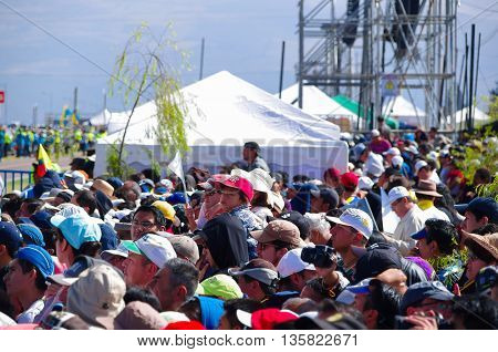 QUITO, ECUADOR - JULY 7, 2015: Lots of people with hats and caps waitting to see pope Francisco, tents behind. Sunny day.