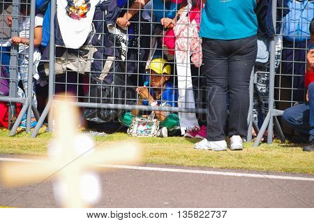 QUITO, ECUADOR - JULY 7, 2015: Little boy praying with a little poster of pope Francisco on the floor, hands together in the middle of people.