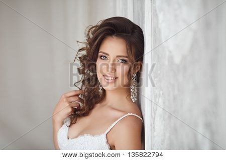Studio Portrait Of Beautiful Bride With Perfect Hairstyle And Makeup.