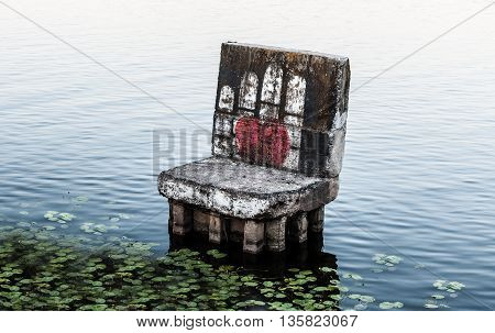 old a concrete armchair in water near the shore