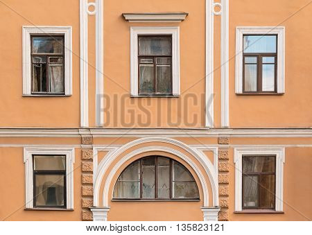 Several windows in a row on facade of urban apartment building front view St. Petersburg Russia