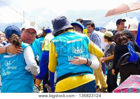 QUITO, ECUADOR - JULY 7, 2015: People giving peace each other in pope Francisco mass, volunteers in a sunny day hugging.