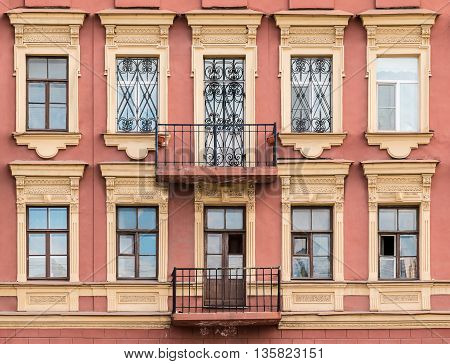 Several windows in a row and balconies on facade of urban apartment building front view St. Petersburg Russia