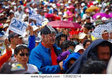 QUITO, ECUADOR - JULY 7, 2015: In the middle of thousand people, a big man with blue pull is praying, holding a jacket.