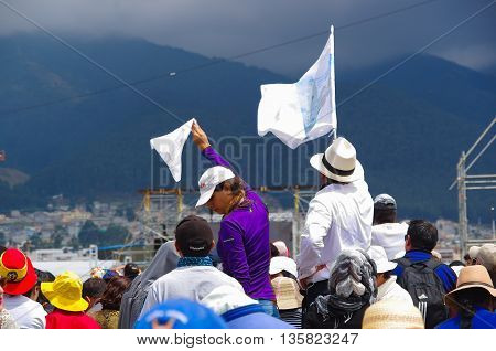 QUITO, ECUADOR - JULY 7, 2015: Crowded event of pope Francisco mass, two persons holding white flags, peace symbol.