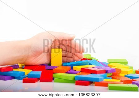 Hand playing with colored domino on white background
