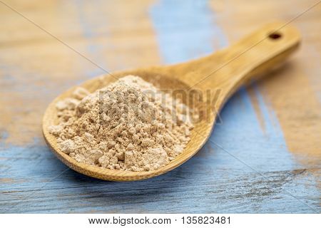 red maca root powder on a wooden spoon  against painted wood