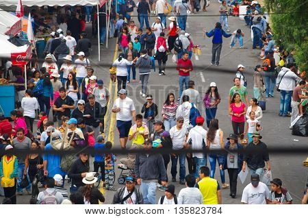 QUITO, ECUADOR - JULY 7, 2015: People between lines, walking in a long street. Food shops on the sides.