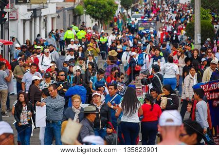 QUITO, ECUADOR - JULY 7, 2015: Crowded avenue with lots of people walking, police watching and guarding people.