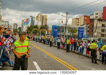 QUITO, ECUADOR - JULY 7, 2015: People on the streets waitting to see or touch to pope Francisco, police guarding outside.