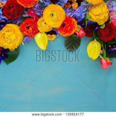 Flowers fresh festive border composition on blue table background with copy space