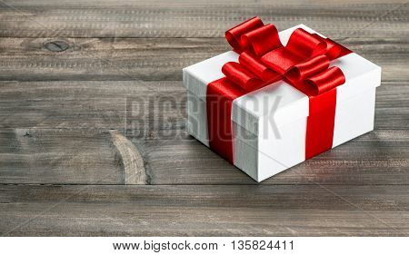 Gift box with red ribbon bow on wooden background. Holidays decoration