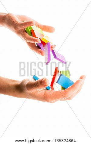 Falling colorful domino off hand on white background