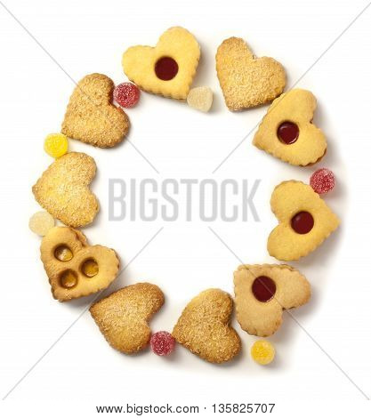 A photo of heart-shaped tea cookies and gum drops forming a circle with copyspace shot from above on white background