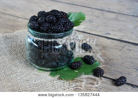 Mulberry berries in a jar on wooden boards