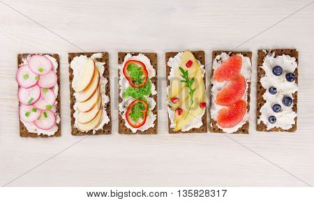 Bruschetta with cream cheese and fresh berries fruits and vegetables. Top view.