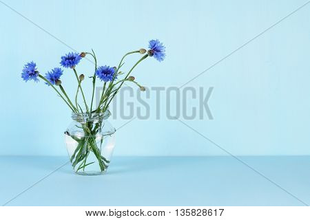 Blue cornflowers in glass jar on turquoise background