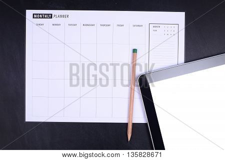Monthly planner with pencil and tablet on black background