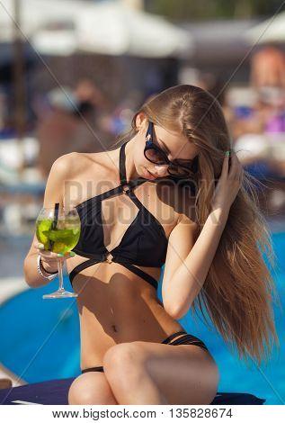 beautiful woman in bikini and sunglasses sitting in swimming pool . Fashionable portrait. Elegant woman in a bikini and sunglasses