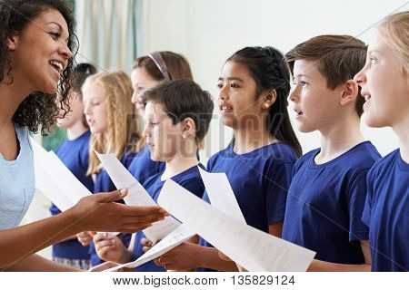 Group Of School Children With Teacher Singing In Choir