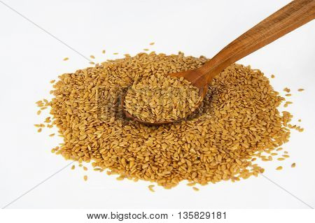 a bunch of  golden flax seed on a white background