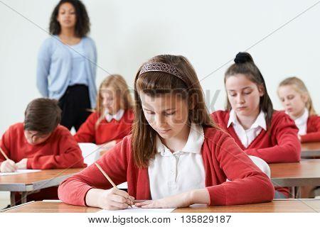 Female Pupil At Desk Taking School Exam