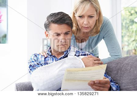 Unhappy Couple Reading Letter About Husband's Injury