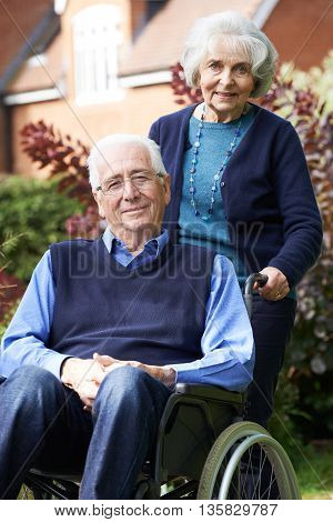 Senior Man In Wheelchair Being Pushed By Wife