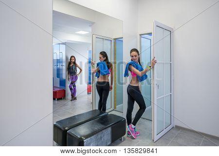Alluring girls posing in locker room of fitness center