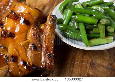 Pork with green beans served on wooden board