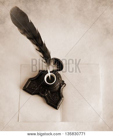 Antique brass inkwell with feather and blank paper card - Sepia toned artwork in retro style