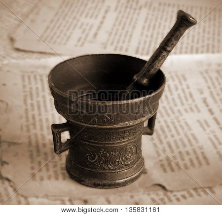 Old bronze mortar and pestle on the pages of ancient book with effect of shallow depth of field - Sepia toned artwork in retro style