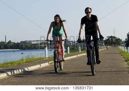 The Girl And The Young Man Ride On A Bicycle In The City