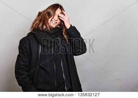 Portrait of handsome fashionable man wearing black coat and scarf. Young guy posing in studio. Winter or autumn fashion.