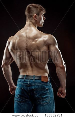 Muscular bodybuilder guy doing posing over black background. He turned his back