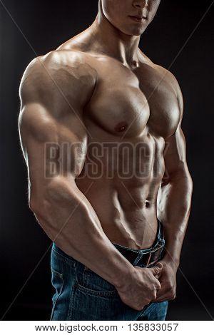 Muscular bodybuilder guy doing posing over black background. Naked torso in jeans. Close-up