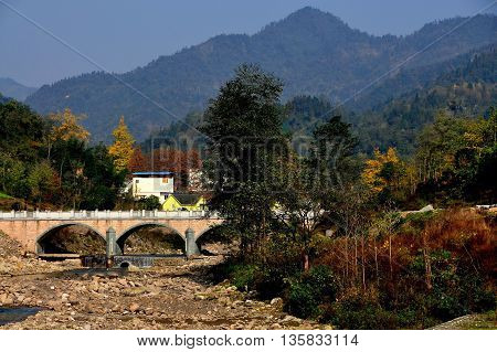 Bai Lu China - November 17 2013: A rocky river bed spanned by an arched bridge with distant mountains