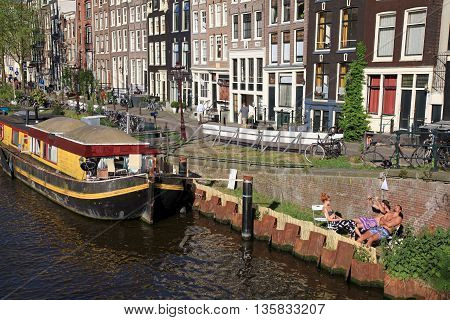 AMSTERDAM, NETHERLANDS - MAY 8, 2016: People relax on canal embankment near houseboat in Amsterdam, Netherlands. Houseboats are high demand very popular and common form of housing in Amsterdam